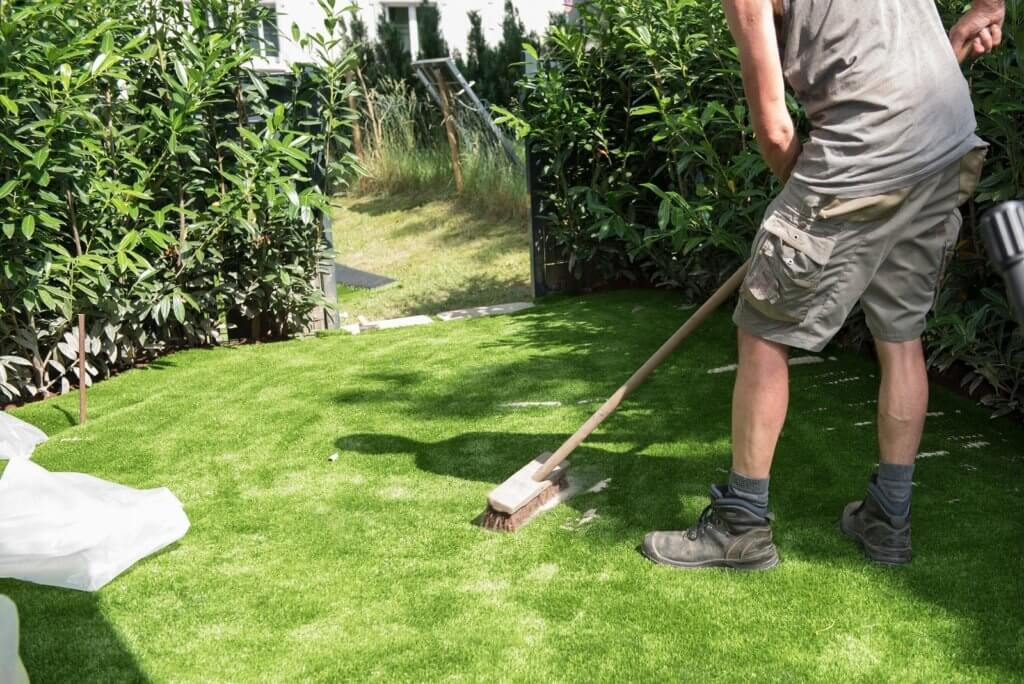 man sweeping artificial grass